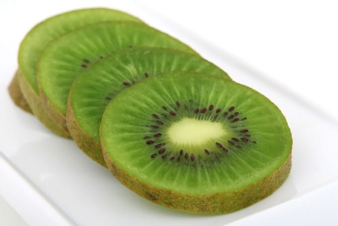 Slices of kiwi fruit on a white plate