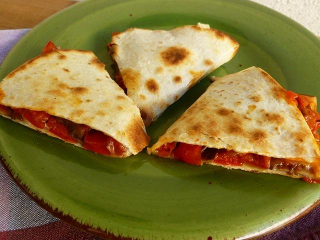 Pepper, Onion and Mushroom Quesadilla cut in three wedges on green plate.