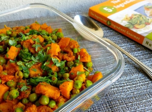 Skinny Curried Sweet Potatoes with Green Peas in glass dish with spoon.