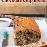 Loaf of Banana Bran Chocolate Chip Bread with a few slices laying on a table with a knife.