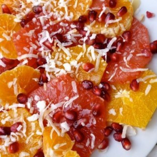 sliced oranges, pink grapefruit slices with coconut and pomegranate arils from above white plate