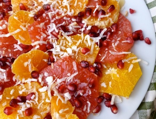 Sliced oranges, pink grapefruit slices with coconut and pomegranate arils from above on white plate