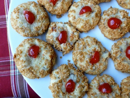 Plate of old-fashioned Wheaties cookies topped with maraschino cherries from above.