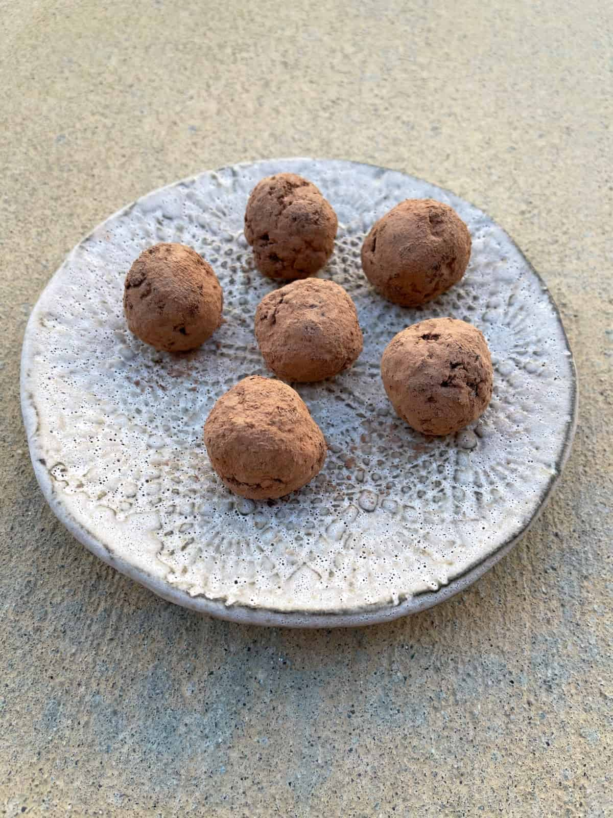 Cranberry chocolate truffles coated in cocoa powder on ceramic plate.