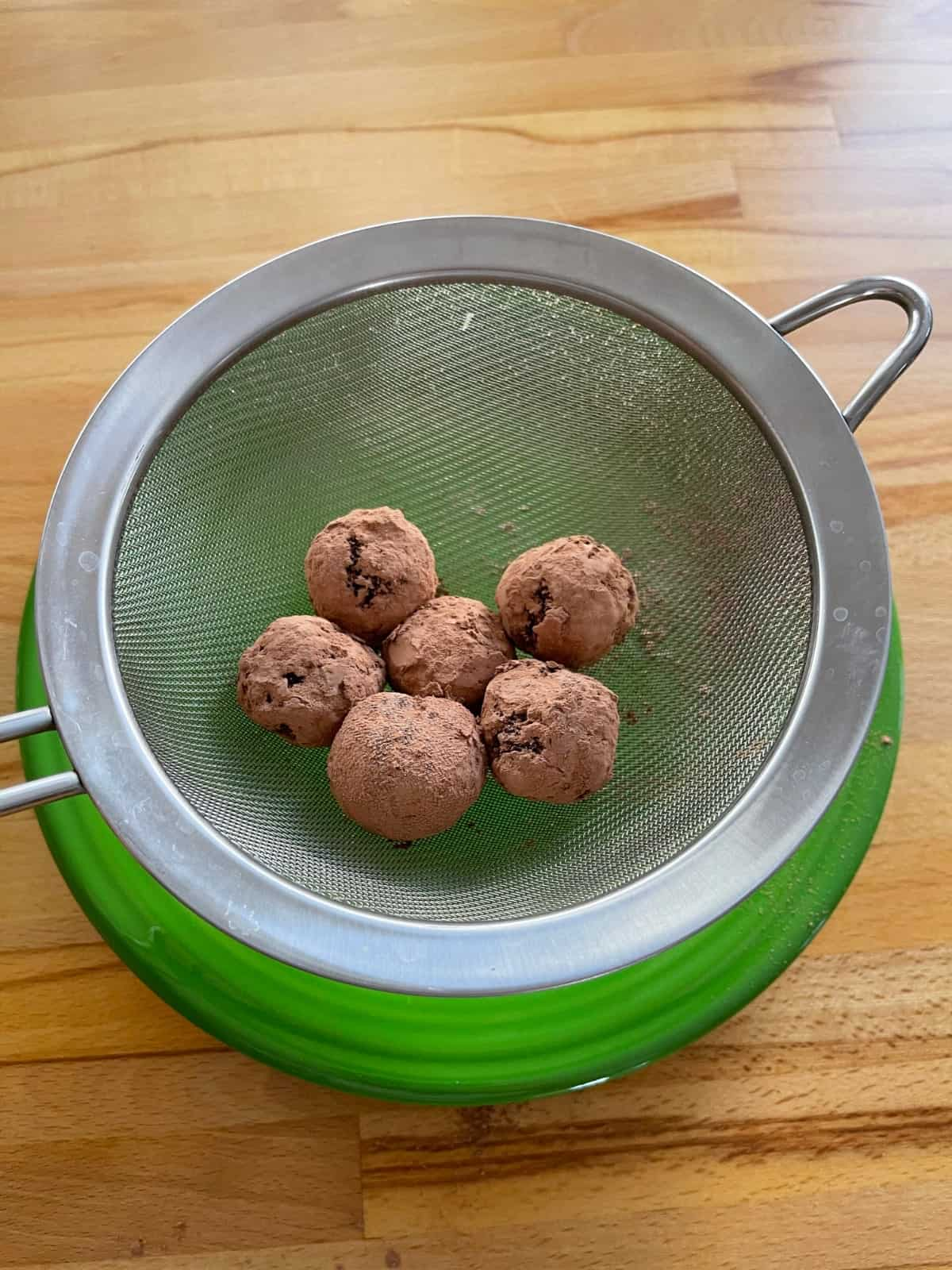 Cranberry chocolate truffles in sieve over green plate.