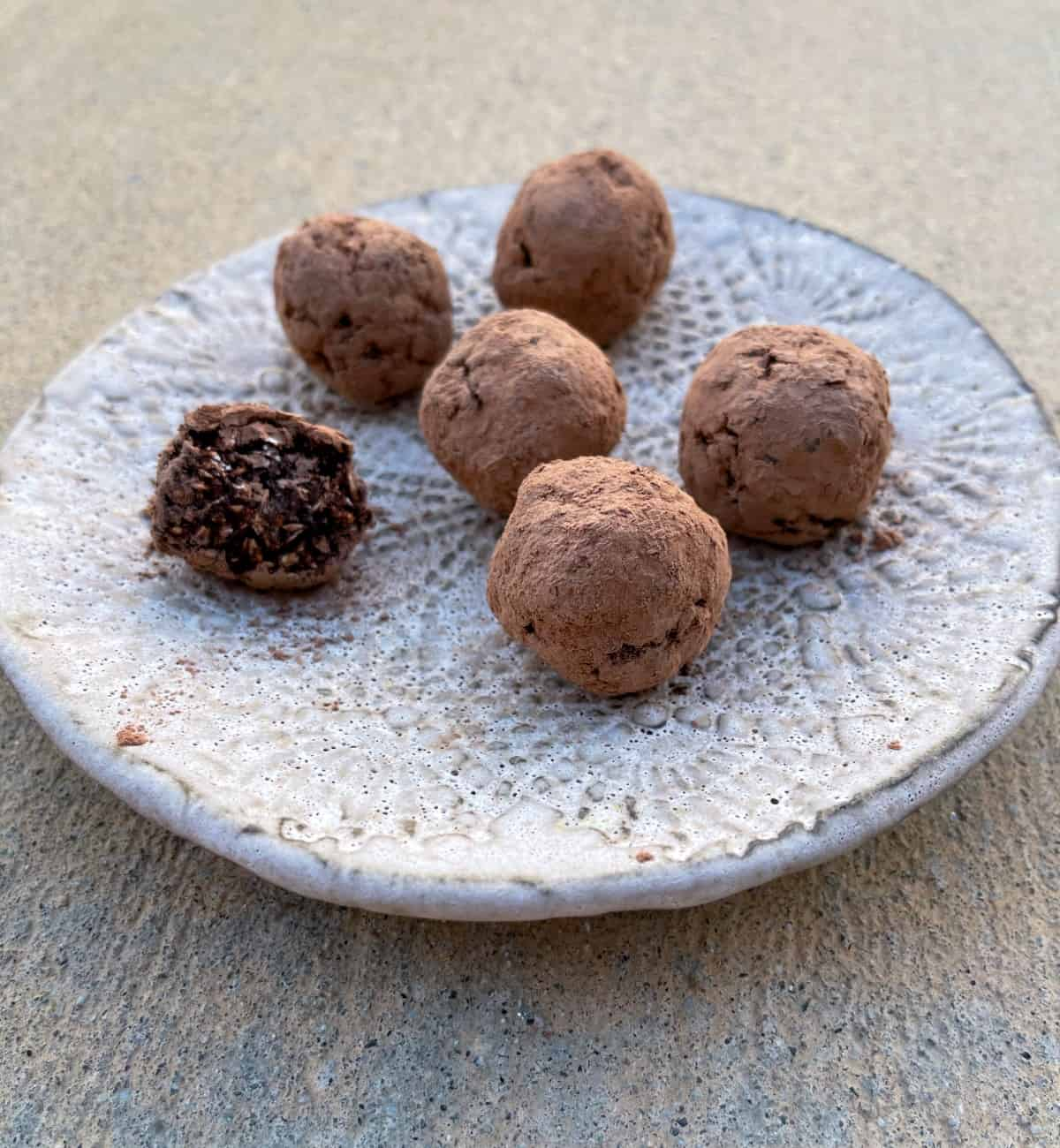 Cranberry chocolate truffles on ceramic plate with bite out of one truffle.