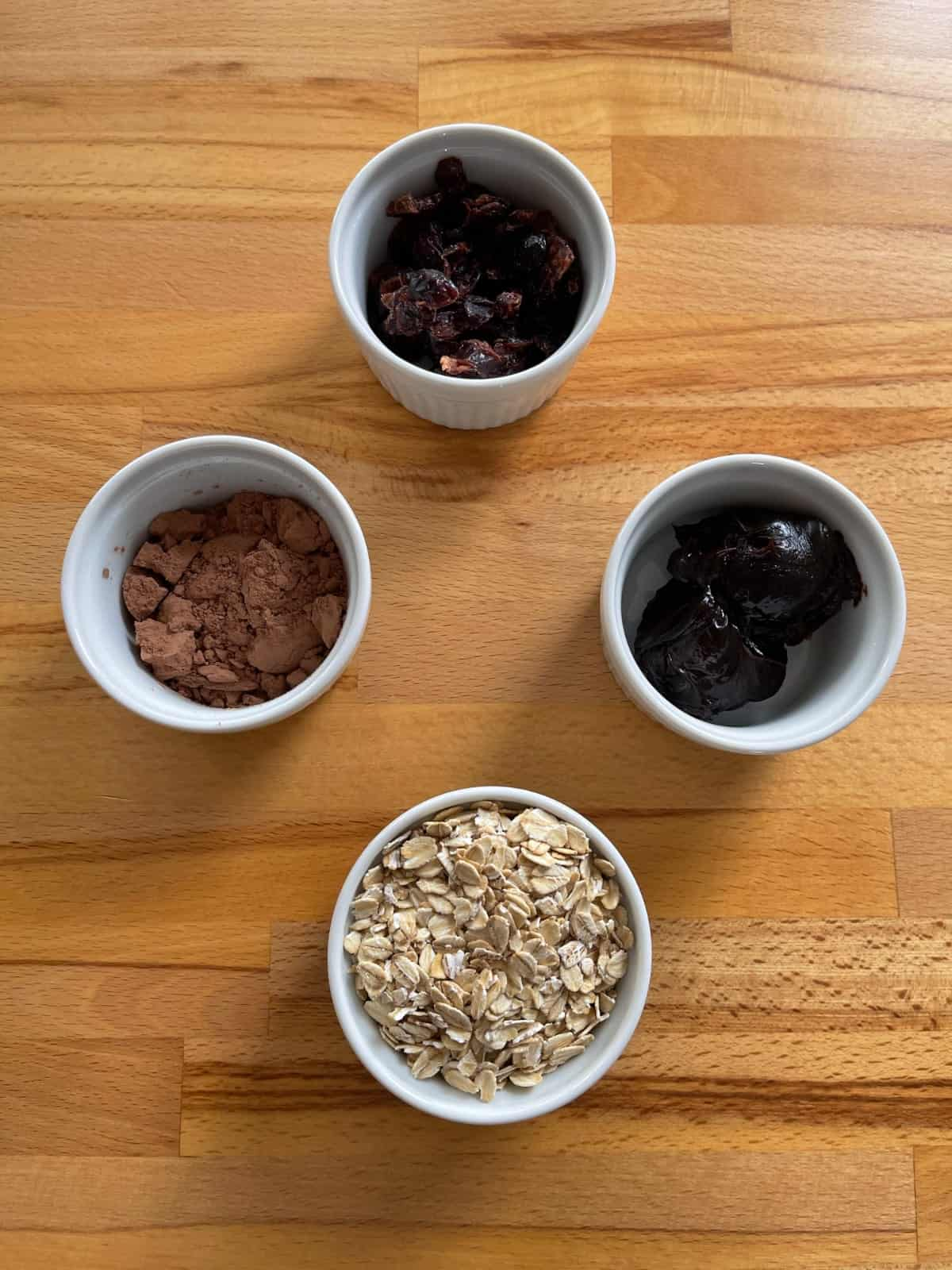 Hot fudge, dried cranberries, cocoa powder and rolled oats in small white ramekins on wood table.