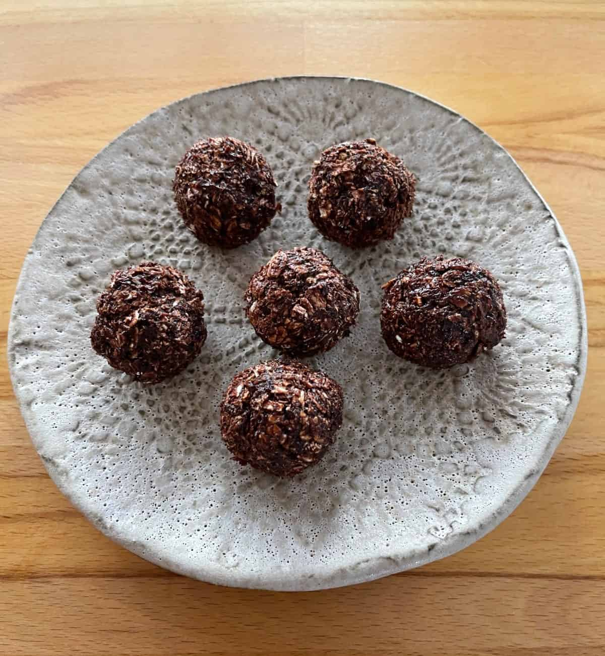 Rolled cranberry chocolate truffles on brown ceramic plate on wood table.