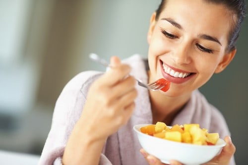 Woman smiling while holding a fork up to her mouth and holding a bowl of fresh fruit