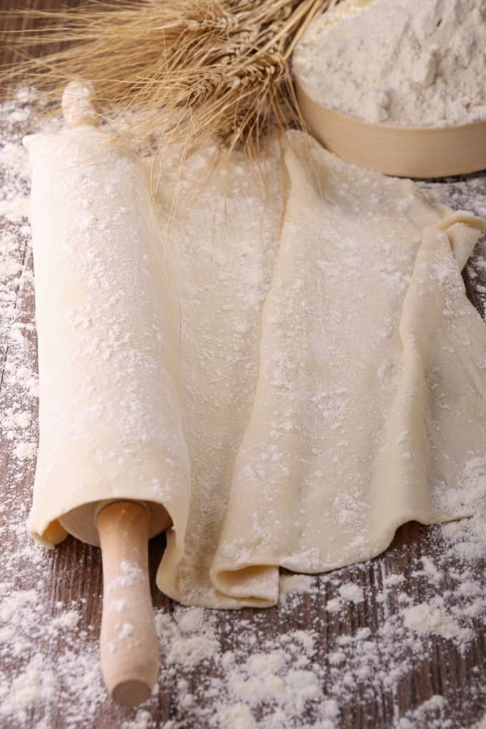 Flatbread dough with a rolling pin and bowl of flour