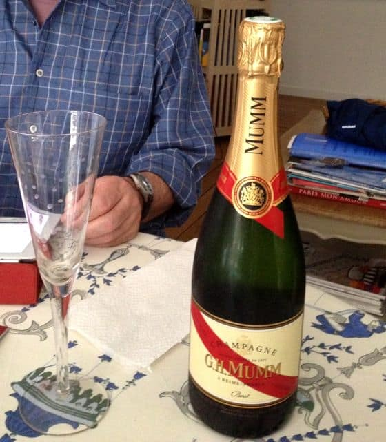 Bottle of Mumm Champagne on a table with a champagne flute