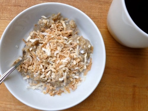 Toasted Coconut Banana Breakfast Pudding in white bowl with spoon and mug of black coffee.