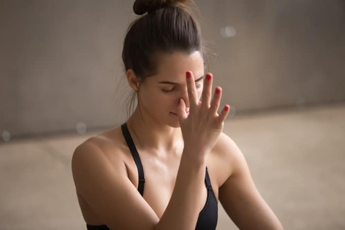 Young woman practicing alternate nostril breathing