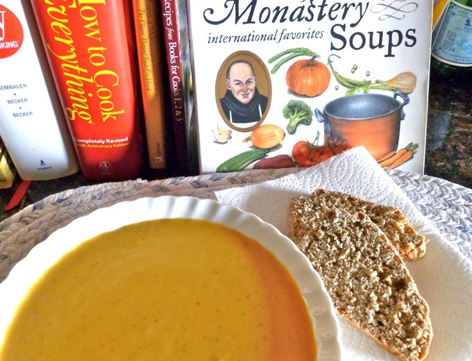 Bowl of Irish Cheddar Soup with two pieces whole grain toast and collection of cookbooks in the background