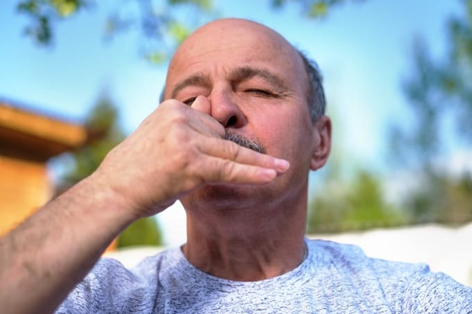 Man with mustache practicing alternate nostril breathing