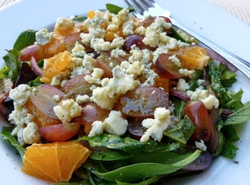 Salade Francaise-Espagnole with mixed greens oranges, grapes and crumbled blue cheese on white salad plate with a fork.
