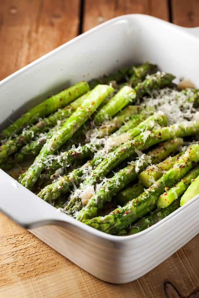 Roasted Asparagus topped with Parmesan cheese and crushed red pepper in a white dish