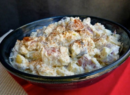 Creamy Red, White and Blue Potato Salad in blue bowl on red mat