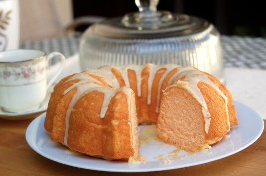 Easy Orangsicle Cake Mix Bundt Cake with icing on cake plate with slice missing.