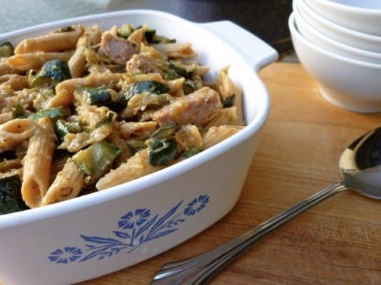 Penne pasta with sausage and zucchini in a white serving dish on a wooden table