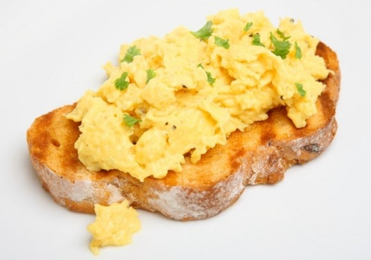 scrambled eggs on a slice of toast sprinkled with herbs