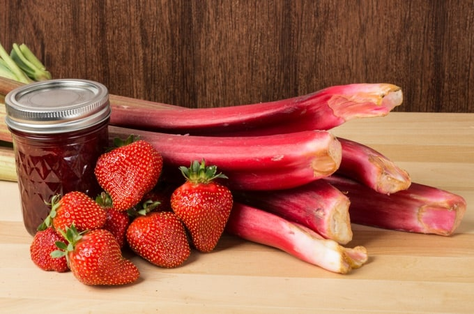 Jar of strawberry rhubarb jam with fresh strawberries and rhubarb