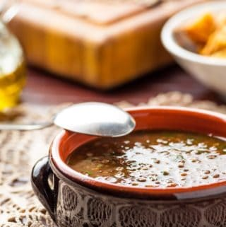 Bowl of vegetable beef lentil soup with a spoon