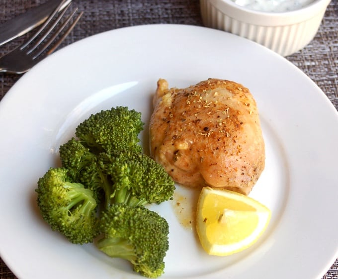 Baked lemon chicken thigh on white dinner plate with steamed broccoli and lemon wedge.