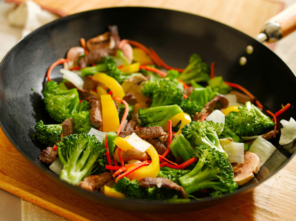 Beef and broccoli with bell peppers in wok.