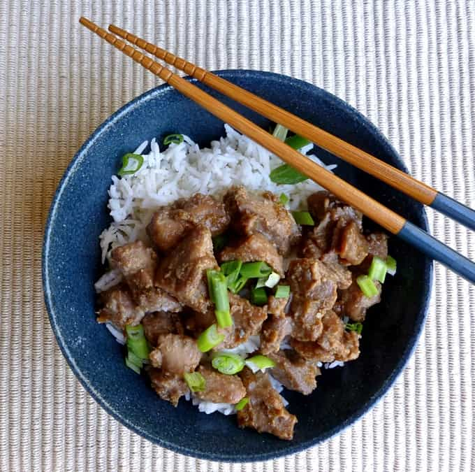 Chicken teriyaki over rice with sliced green onion in blue bowl with chop sticks.