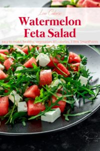 Watermelon feta salad with arugula on black plate with fresh watermelon slices in background.