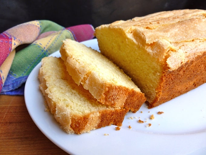 Madeira loaf cake with two cut slices on white cake plate.