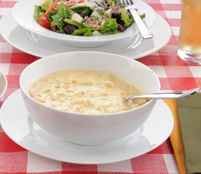 Bowl of corn chowder with a mixed green salad on a table with a red checkered table cloth