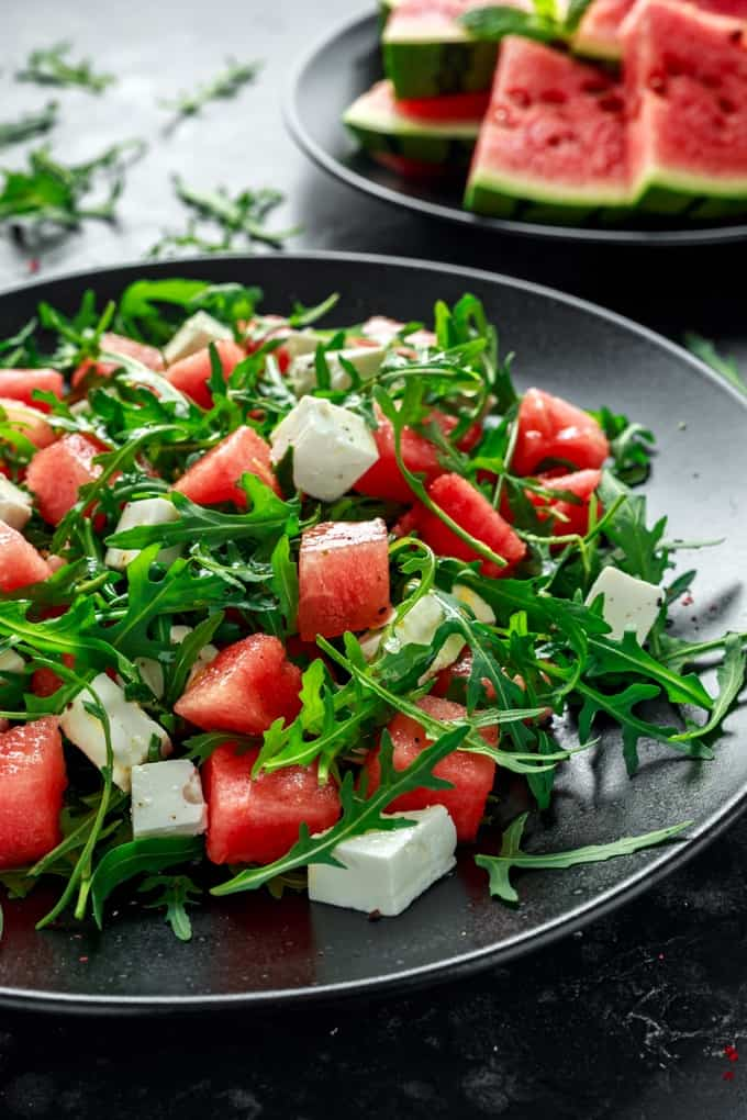 Watermelon, Feta and Arugula Salad on a black plate with a plate of watermelon slices in the background