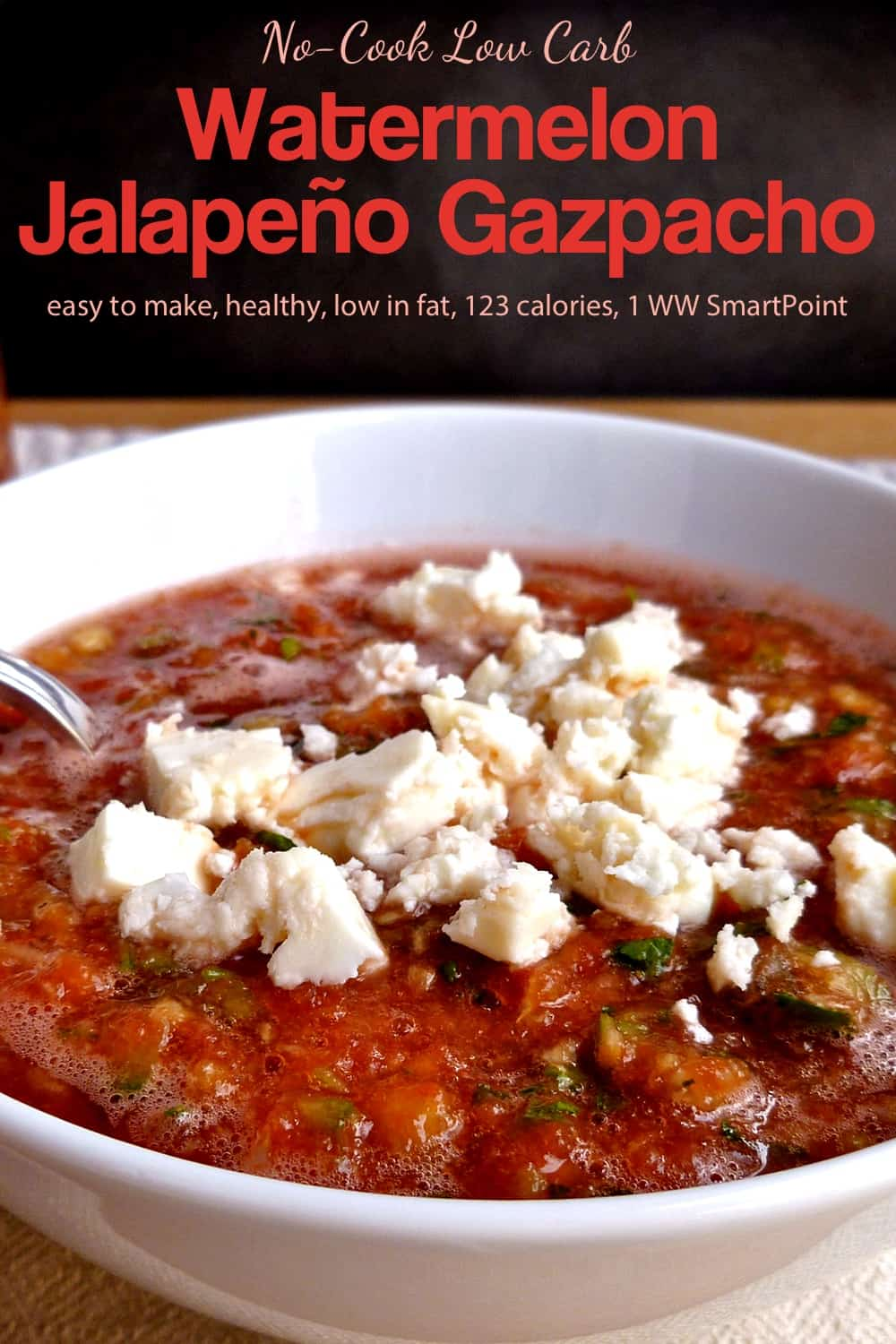Chilled watermelon gazpacho garnished with crumbled feta cheese in a white bowl.