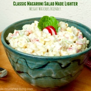 classic macaroni salad in green pottery bowl wood table