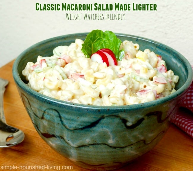 Classic macaroni salad in green pottery bowl on wood table