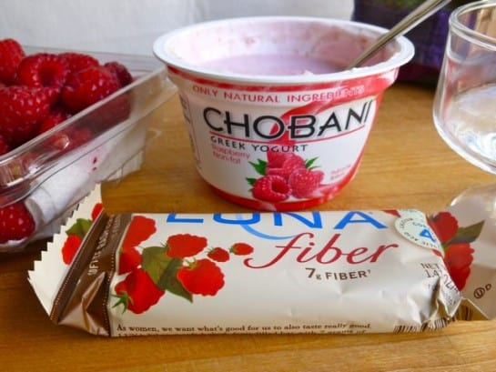 Container of Chobani Greek Raspberry Yogurt, fresh raspberries and a chocolate raspberry Luna Fiber Bar.