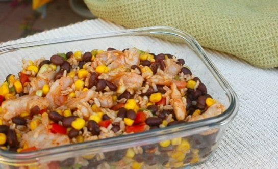 Shrimp Black Bean Salad with rice and corn in glass rectangle container on beige mat