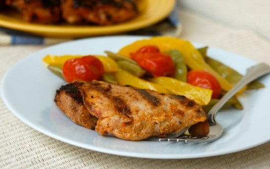 Spicy Grilled Chicken Thighs on white plate with grilled vegetables