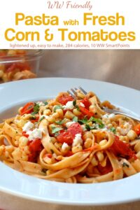 Fettuccine pasta with fresh corn and tomatoes garnished with crumbled cheese and fresh herbs in white bowl with fork.