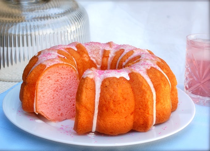 Pink lemonade bundt cake with icing and slice removed on white plate with glass of pink lemonade.