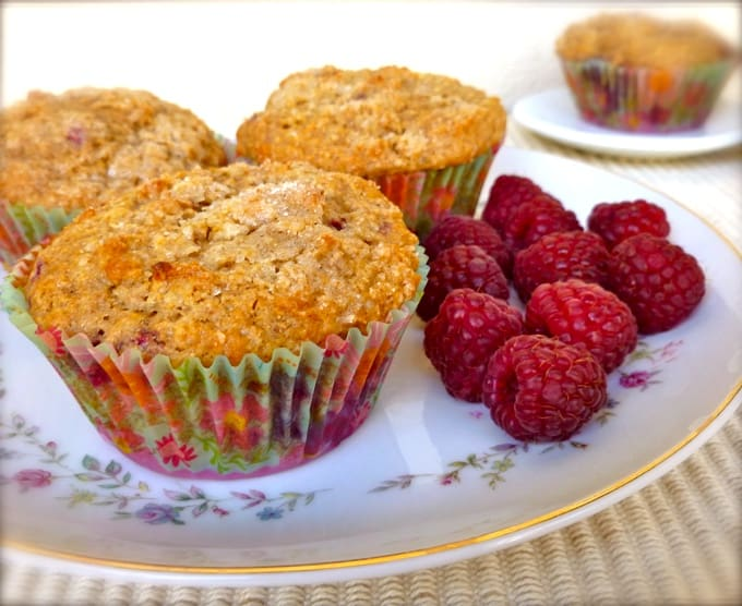 Three raspberry oatmeal muffins on flowered plate with fresh raspberries and another muffin in the background.