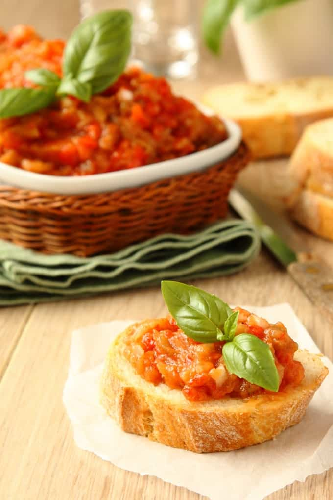 Slice of baguette topped with eggplant spread and fresh basil with dish of eggplant spread in the background.