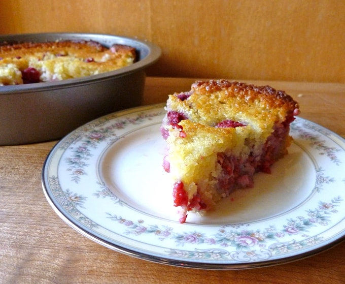 Slice of fresh raspberry cake on china with whole cake in background.