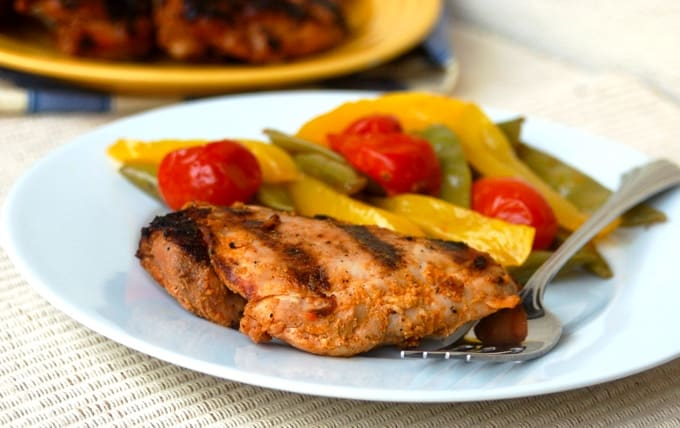 Spicy grilled chicken thigh with vegetables on white plate.