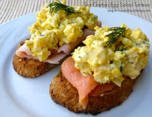Open-faced egg salad sandwiches (Tartines) on toasted bread with smoked salmon and fresh dill