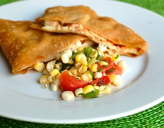 Fresh corn tomato salsa with chicken quesadilla on white plate.