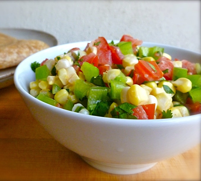 Fresh corn tomato salsa in white bowl on wood table.