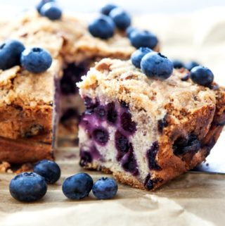 Piece of homemade blueberry crumb cake with fresh blueberries scattered around